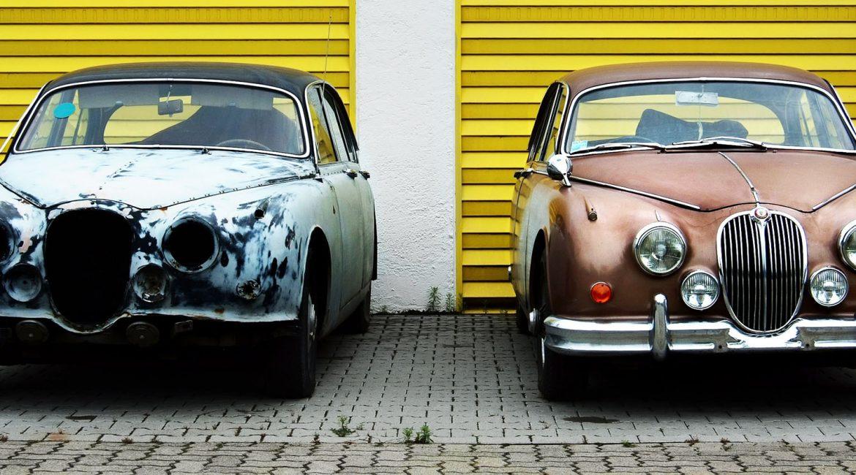 altes und neues Auto vor Garagen