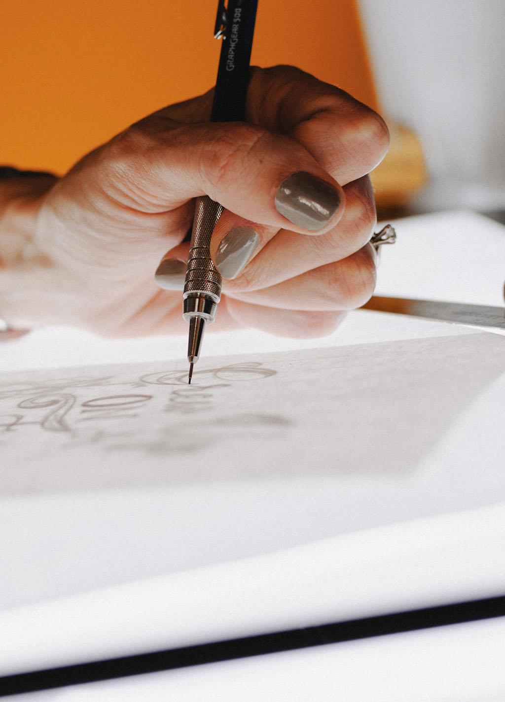 Hand, die mit einem Bleistift auf einem Leuchttisch zeichnet